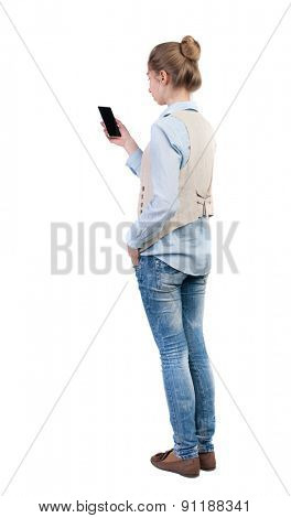 back view of standing young beautiful  woman  in vest and using a mobile phone. Rear view people collection.  backside view of person.  Isolated over white background. Bored girl staring at the phone.
