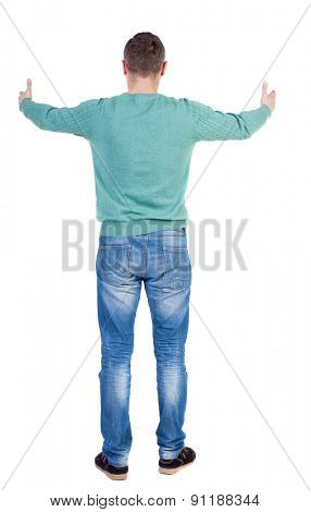 Back view of man in jeans. Standing young guy. Rear view people collection.  backside view of person.  Isolated over white background. The guy in the green jacket shows the big finger with both hands.
