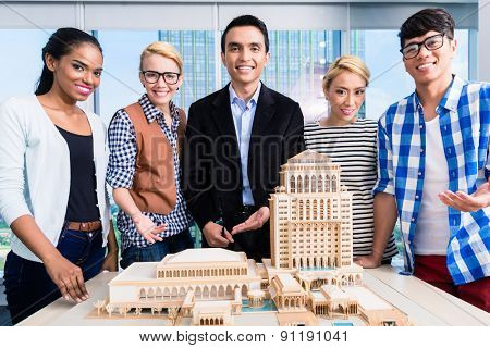 Team of architects presenting model building in presentation to customer