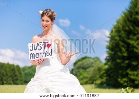 Wedding bride standing hitchhike at street with