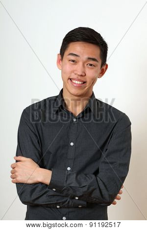 Laughing young Asian man with crossed hands looking at camera.