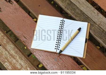 Notebook And Pen On The Brown Bench