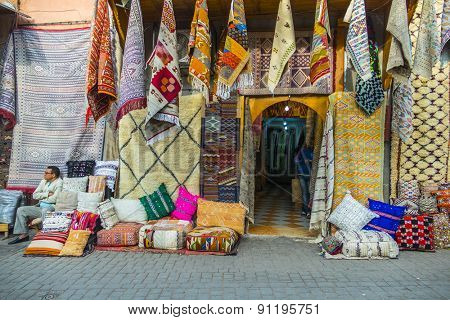 MARRAKESH, MOROCCO, APRIL 4, 2015: Local seller offers textile souvenirs in souks