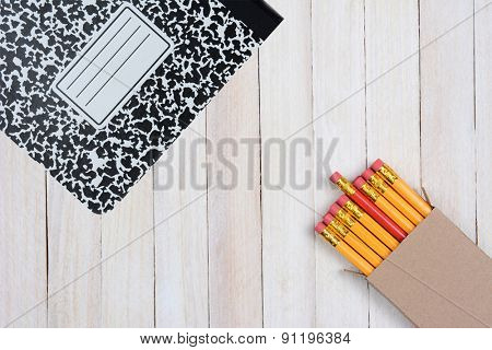 High angle shot of a box of pencils and a composition book on a white wood surface. Objects are in opposite corners of the frame.