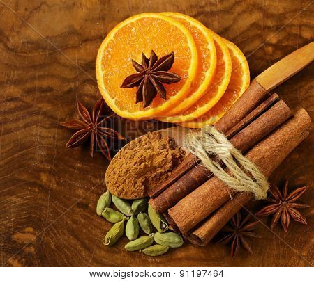 fragrant cinnamon sticks, star anise, cardamom and orange on a wooden background
