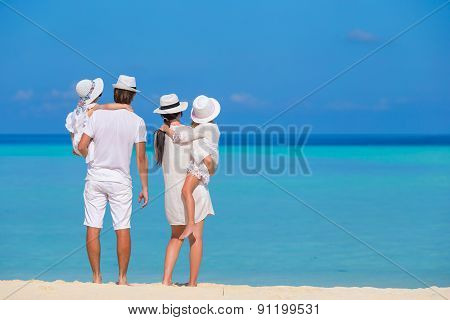 Young family of four on white beach
