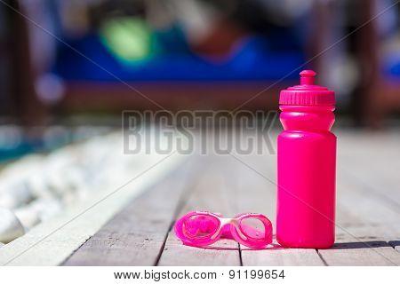 Pink sporty water bottle near swimming pool