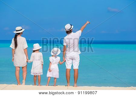 Happy family of four on white beach vacation