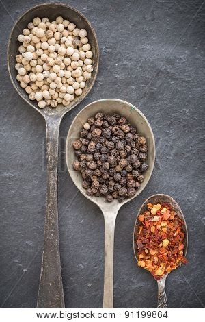 Black Pepper Corn, White Pepper Corn And Dried Chili Flakes In Old Vintage Spoons On Gray Stone Back