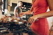 stock photo of human egg  - Closeup image of woman cracking an egg into a frying pan with man standing in background in kitchen. Preparing breakfast.