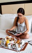 picture of nightgown  - Above view of woman wearing glasses and nightgown relaxing in bed reading book - JPG
