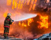 pic of firemen  - Fireman extinguishes a fire in an old wooden house - JPG