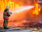 image of firemen  - Fireman extinguishes a burning old wooden residential house - JPG