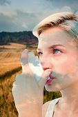 pic of inhalant  - Blonde woman taking her inhaler against blue sky - JPG