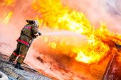 pic of fire extinguishers  - Fireman extinguishes a fire in an old wooden house - JPG