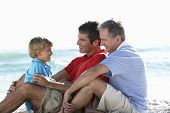 stock photo of grandfather  - Grandfather With Grandson And Father Embracing On Beach Holiday - JPG