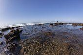 pic of tide  - Rocky coastline low tide ocean reef exposed beach landscape - JPG