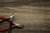 stock photo of pliers  - Two jewelry pliers on a wooden background - JPG