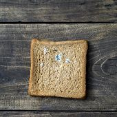 image of taint  - moldy bread on wooden table from above - JPG