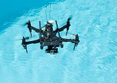 picture of drone  - Flying black drone with camera above water - JPG