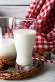 pic of caw  - Milk in glassware with walnuts and cookies on wooden table with napkin - JPG