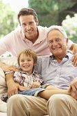 foto of grandfather  - Grandfather With Son And Grandson Laughing Together On Sofa - JPG