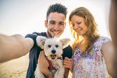 stock photo of pov  - Portrait of young happy couple with dog taking a selfie  - JPG