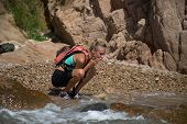 picture of wild adventure  - Adventure girl wash her face in the wild river - JPG