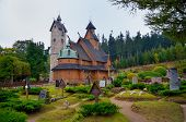 stock photo of graveyard  - Norwegian stave church which was transferred to Karpacz town in Karkonosze mountains Poland - JPG