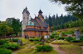 stock photo of graveyard  - Norwegian stave church which was transferred to Karpacz town in Karkonosze mountains Poland - JPG