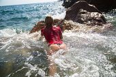stock photo of string bikini  - Sexy girl is swimming to a rock in troubled waters - JPG