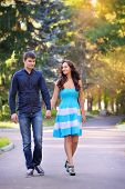 stock photo of stroll  - Couple in love strolling together in a beautiful park - JPG