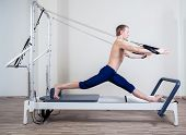 stock photo of pilates  - Pilates reformer workout exercises man at gym indoor - JPG