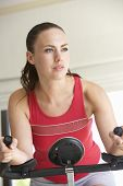 stock photo of exercise bike  - Young Woman On Exercise Bike - JPG