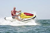 stock photo of jet-ski  - Young guy cruising on the atlantic ocean on a jet ski - JPG
