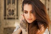 stock photo of indian  - Portrait of a young indian woman in casual style with mehendi on the streets of old city - JPG