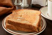 picture of whole-wheat  - Hot buttered whole wheat toast on a rustic wooden table - JPG