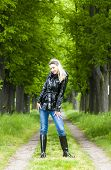 stock photo of woman boots  - woman wearing rubber boots in spring alley - JPG