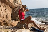 stock photo of string bikini  - Sexy diver girl sitting on the cliff of the rocky beach and preparing her dive - JPG