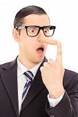 image of cheater  - Vertical shot of a young displeased businessman looking at his long nose and trying to put it back with his finger isolated on white background - JPG