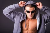 foto of fitness man body  - Guy in a sports jacket and sunglasses - JPG