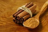 image of cinnamon sticks  - fragrant cinnamon sticks and ground spices on a wooden background - JPG
