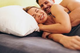 pic of couple  - Happy young couple embracing while lying next to each other on bed - JPG