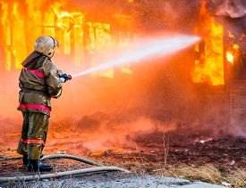 pic of firemen  - Fireman extinguishes a burning old wooden residential house - JPG