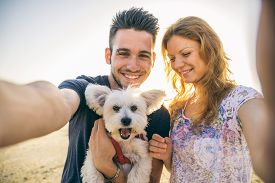 pic of pov  - Portrait of young happy couple with dog taking a selfie  - JPG