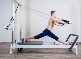 picture of pilates  - Pilates reformer workout exercises man at gym indoor - JPG