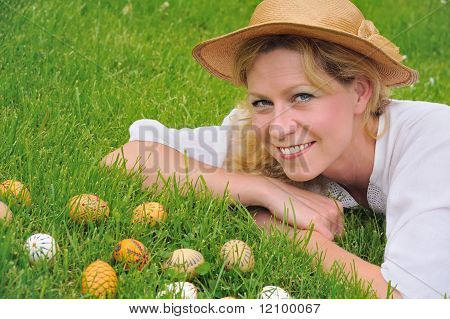 Young woman and easter eggs on the grass