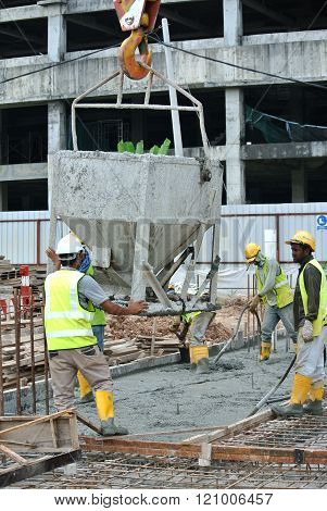 SELANGOR, MALAYSIA - DECEMBER 12, 2015: A group of construction workers pouring raw concrete using concrete bucket into the floor slab form work at the construction site.