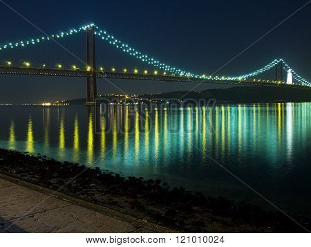 Night view of the April 25 (25 de Abril) Bridge in Lisbon Portugal. Completed in 1966, this suspension bridge across the Tagus River was originally named after dictator Salazar.