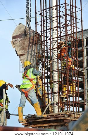 SELANGOR, MALAYSIA - DECEMBER 12, 2015: A group of construction workers pouring concrete using concrete bucket into the column form work at the construction site.